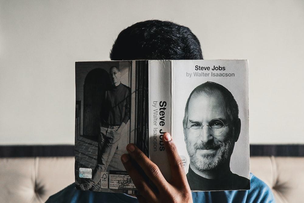 man in black crew neck shirt holding white printer paper