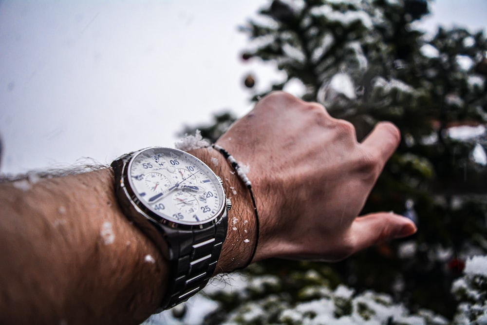 person wearing silver round chronograph watch