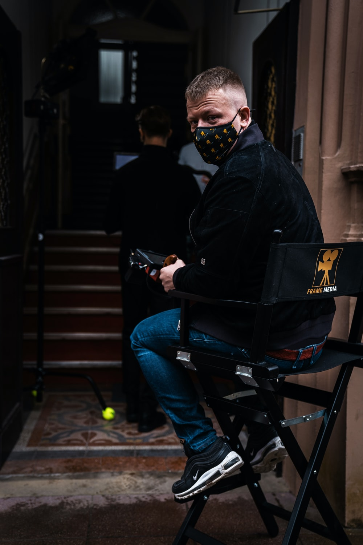 man in black jacket and blue denim jeans sitting on black metal bench
