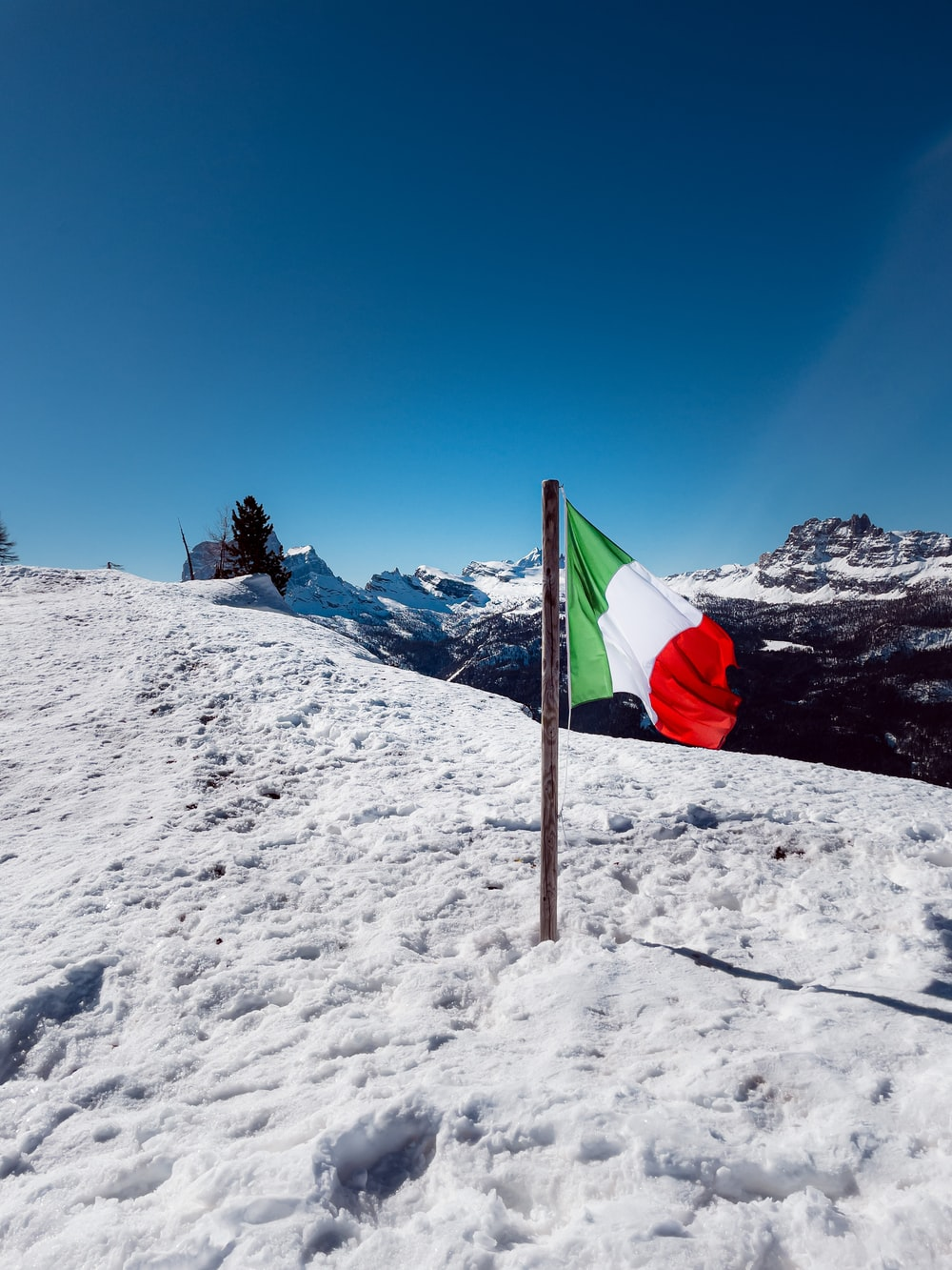 red white and green flag on snow covered mountain under blue sky during daytime
