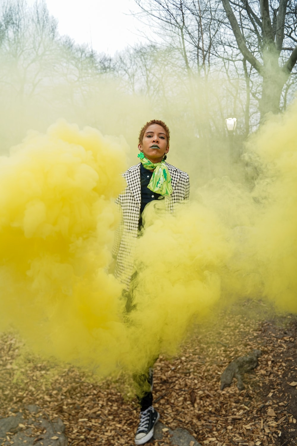 boy in black and white suit standing on ground with yellow smoke