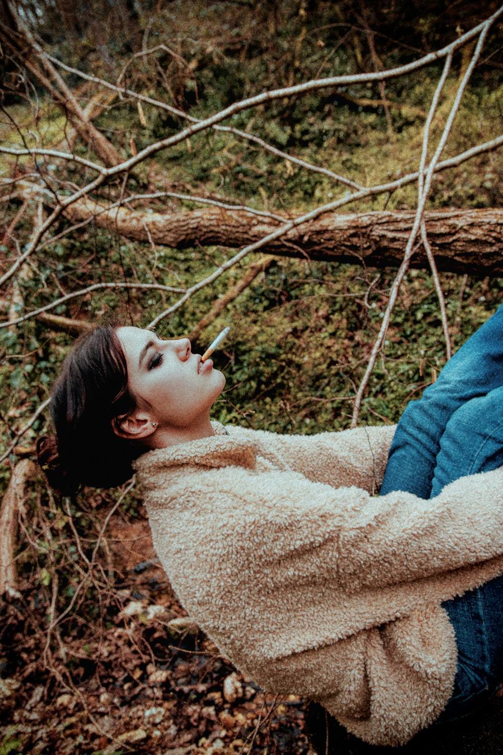 woman in brown sweater lying on brown dried leaves during daytime