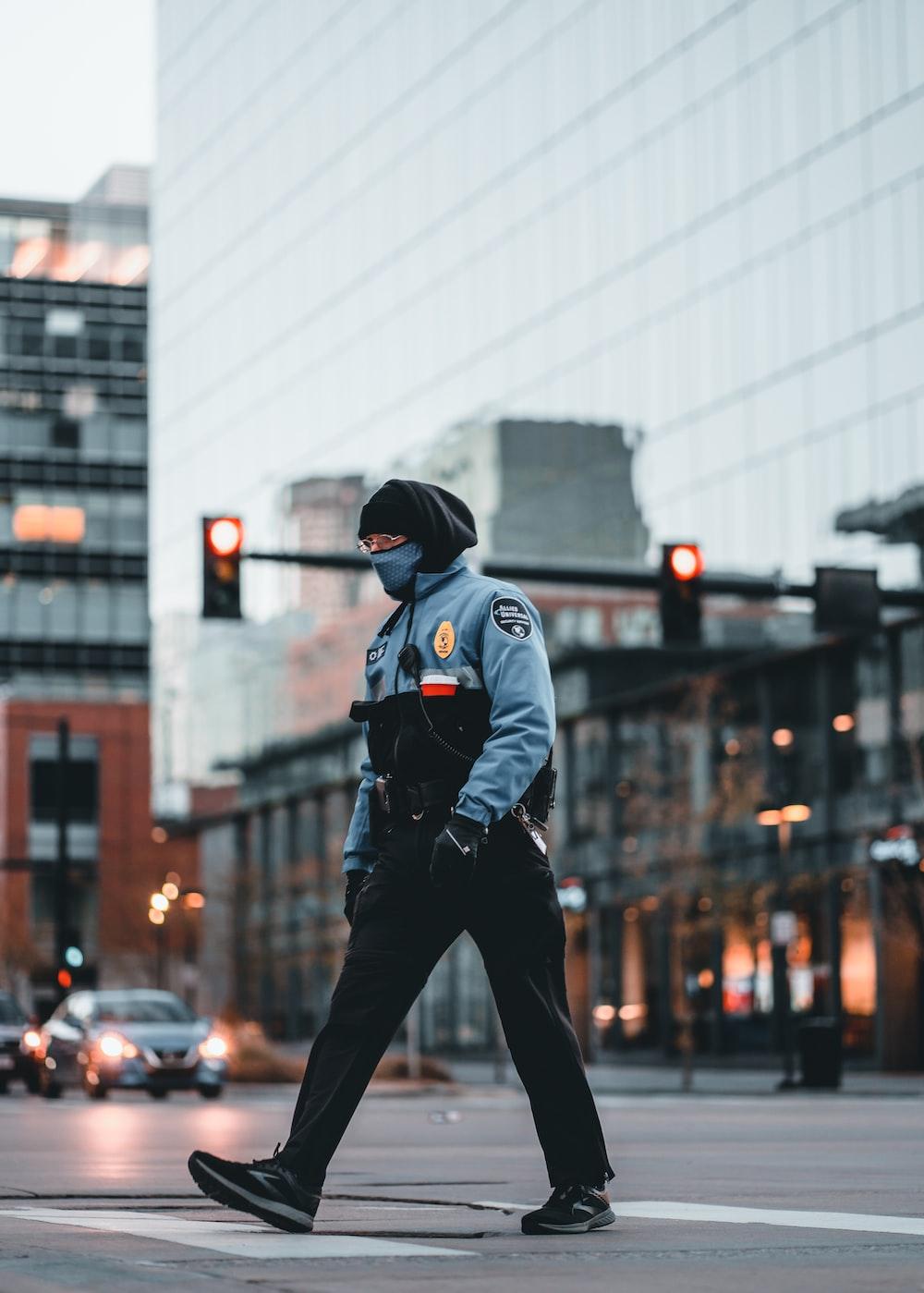 man in black jacket and black pants wearing black cap walking on street during daytime