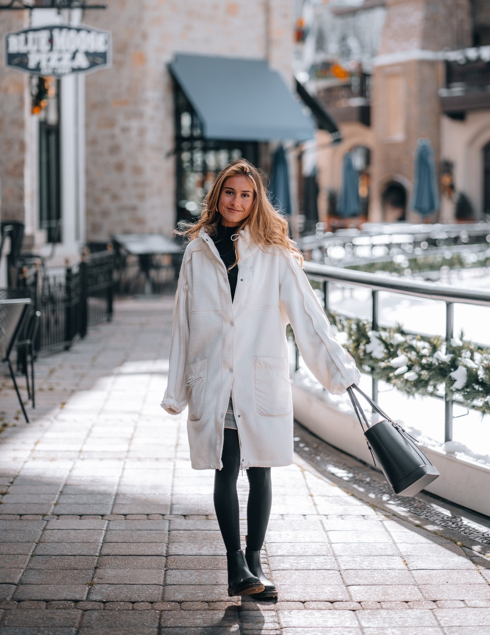 woman in white coat standing on sidewalk during daytime
