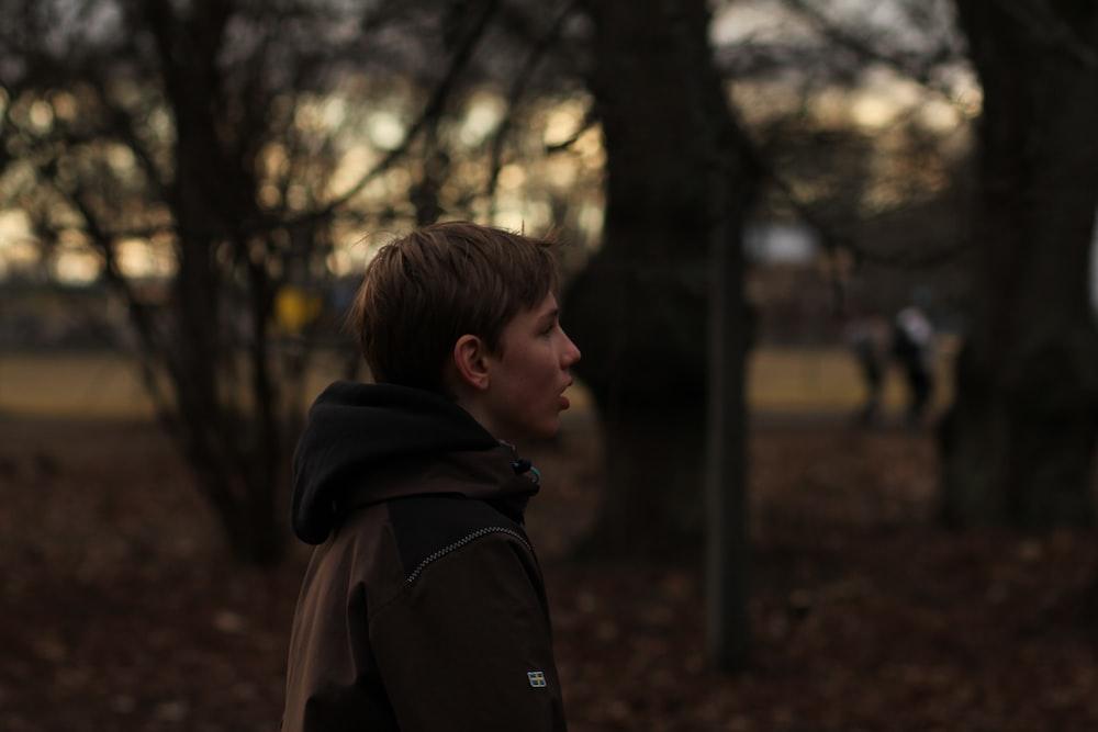 boy in black hoodie standing near trees during daytime