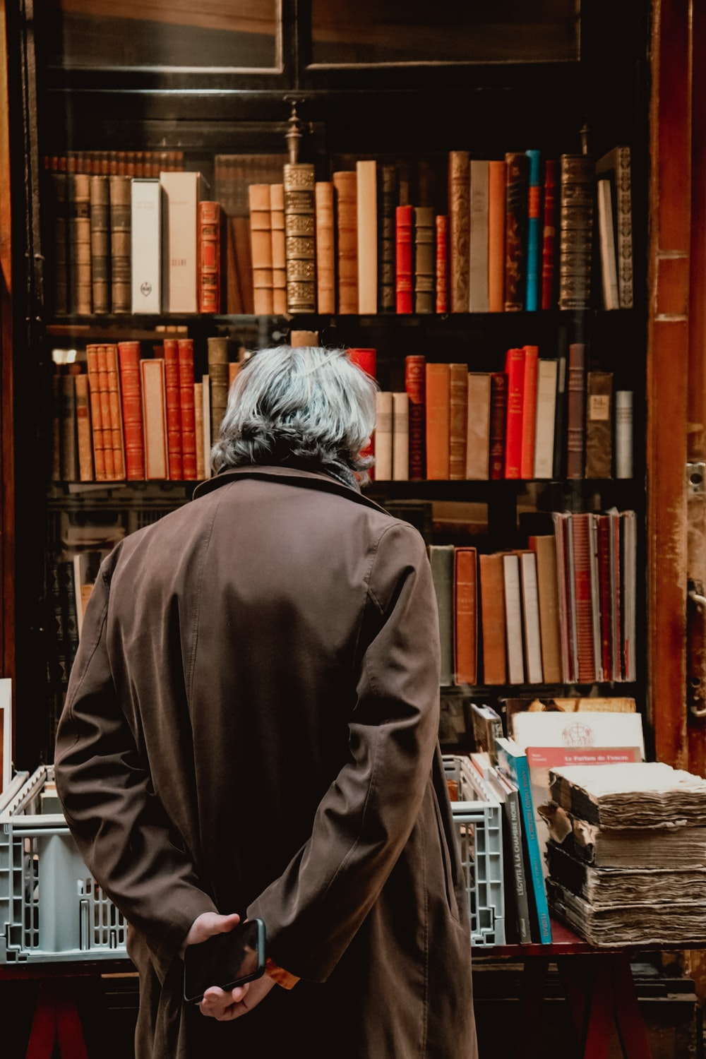 person in gray hoodie standing near books
