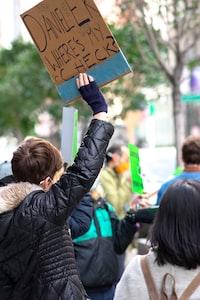 woman in black jacket holding brown wooden board