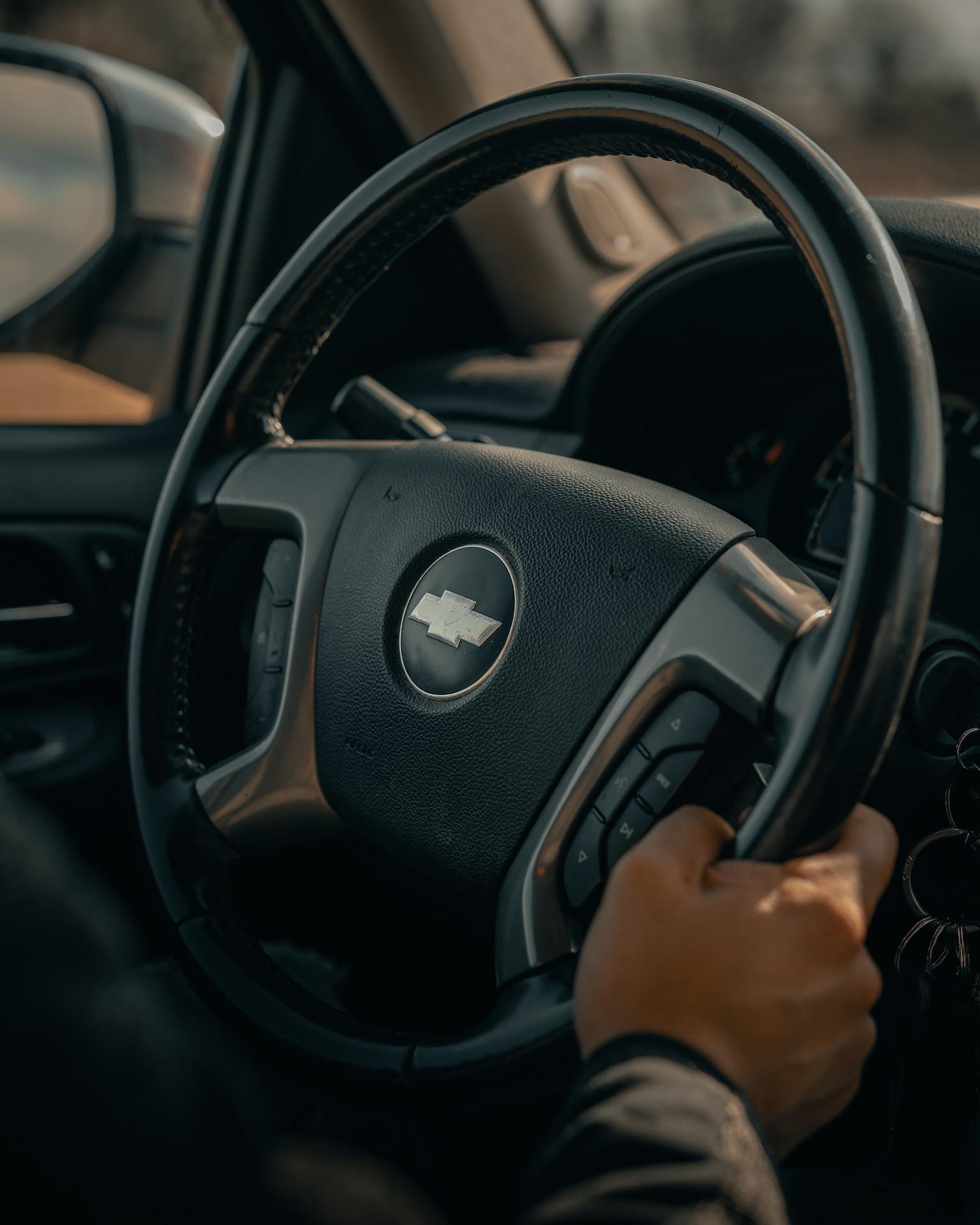 person holding black mercedes benz steering wheel