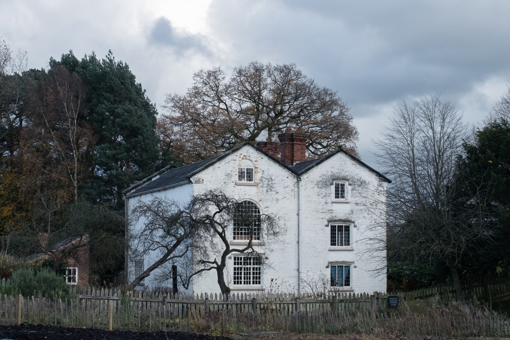 white and brown house surrounded by trees under white clouds during daytime