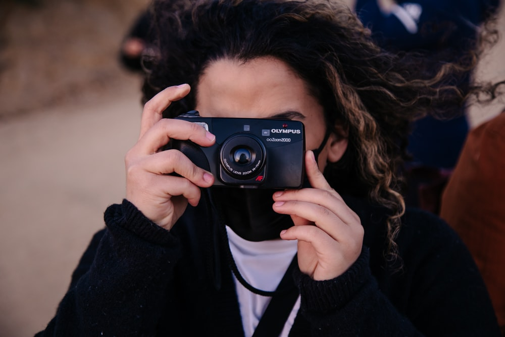 woman in black jacket holding black nikon camera