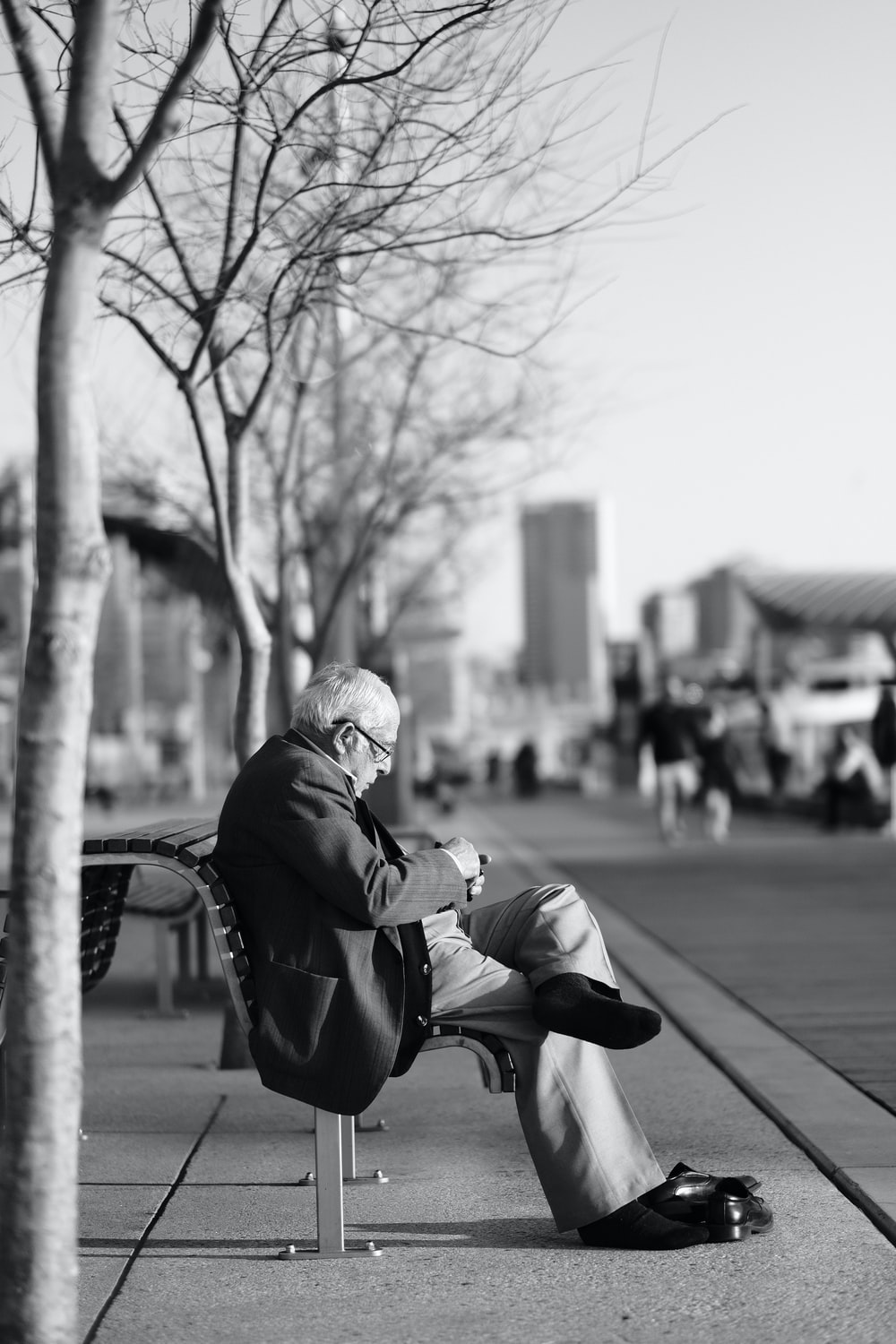 grayscale photo of man sitting on bench near bare trees