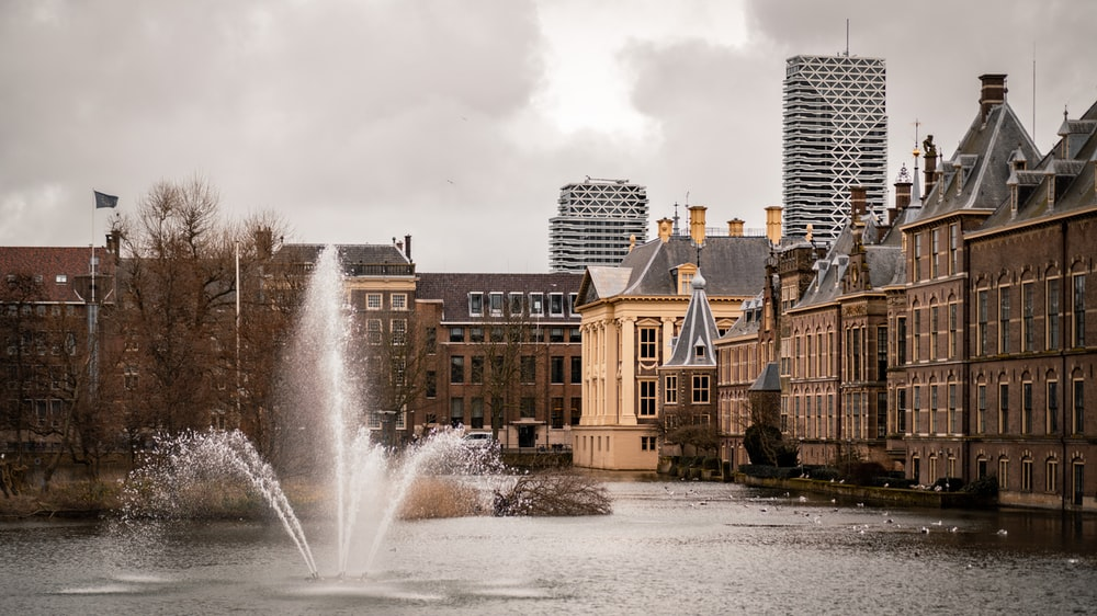 water fountain in the middle of city buildings during daytime