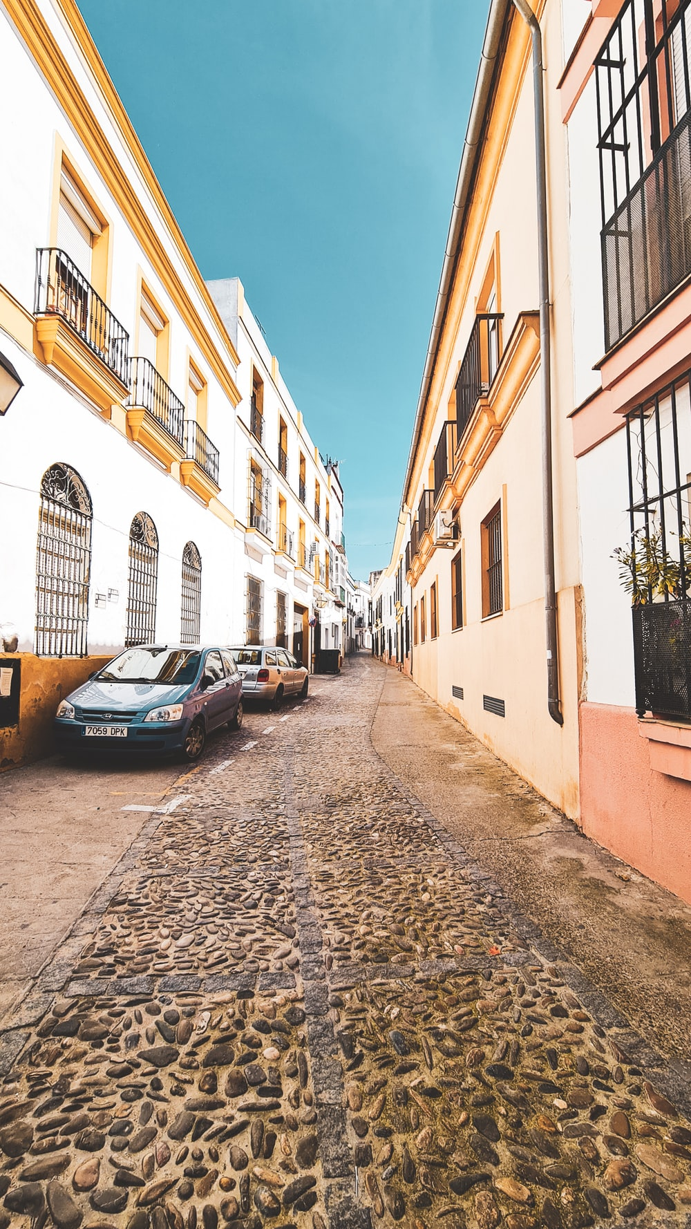 blue car parked beside beige concrete building during daytime