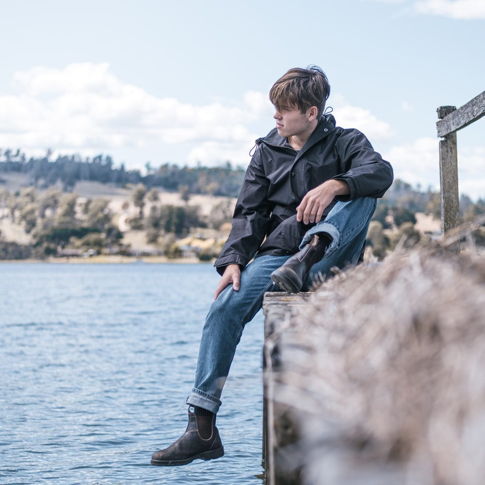 man in black jacket and blue denim jeans sitting on wooden post near body of water