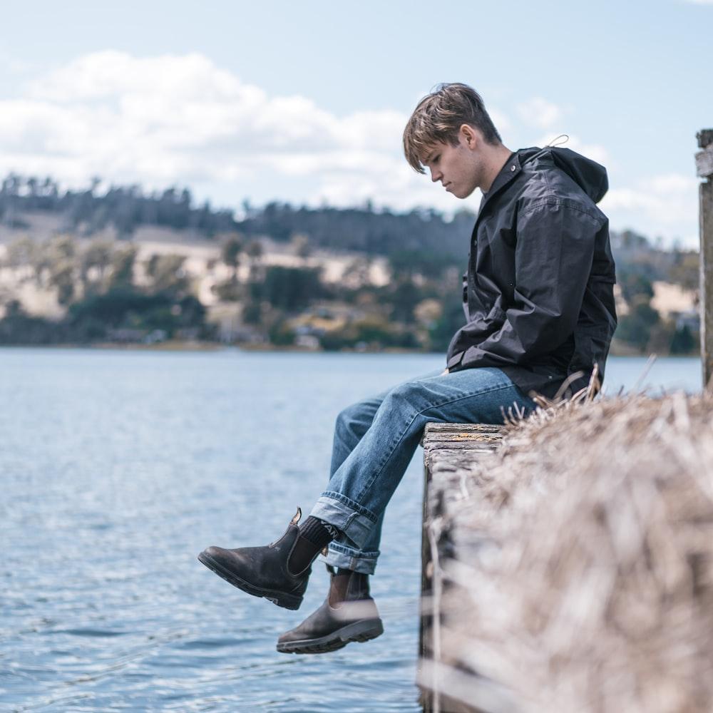 man in black jacket and blue denim jeans sitting on brown wooden log during daytime