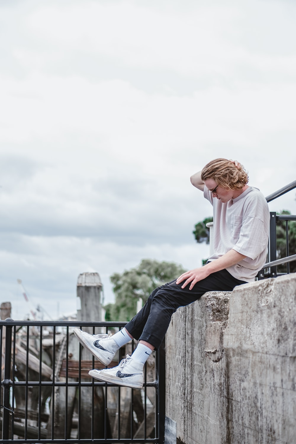 woman in white long sleeve shirt and blue denim jeans sitting on gray concrete fence during