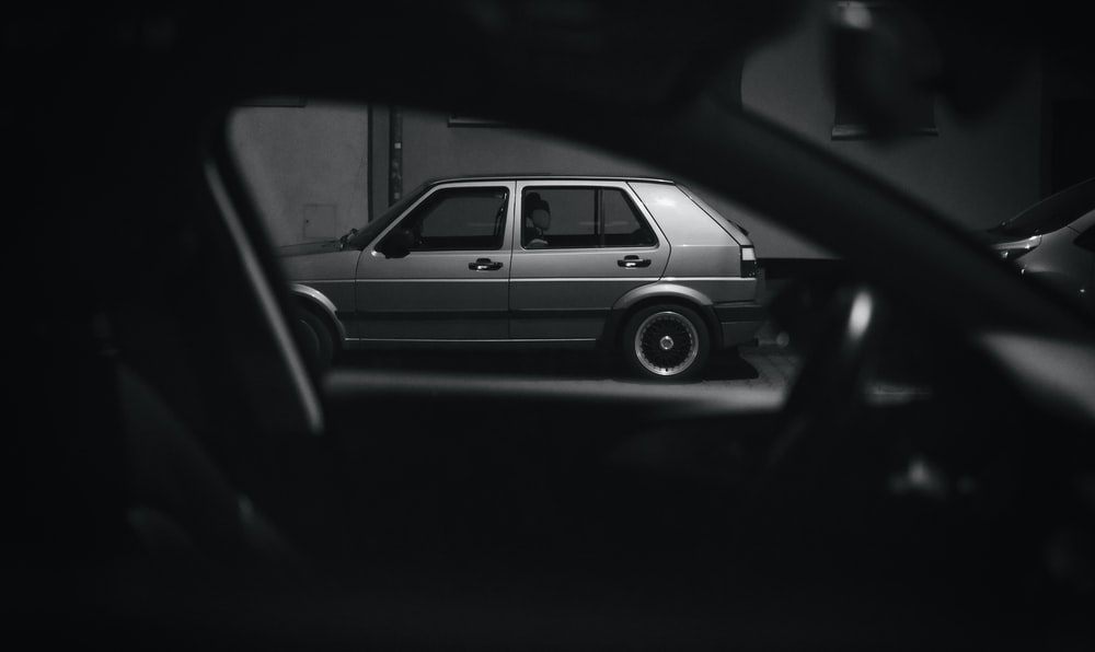 grayscale photo of car in a dark room