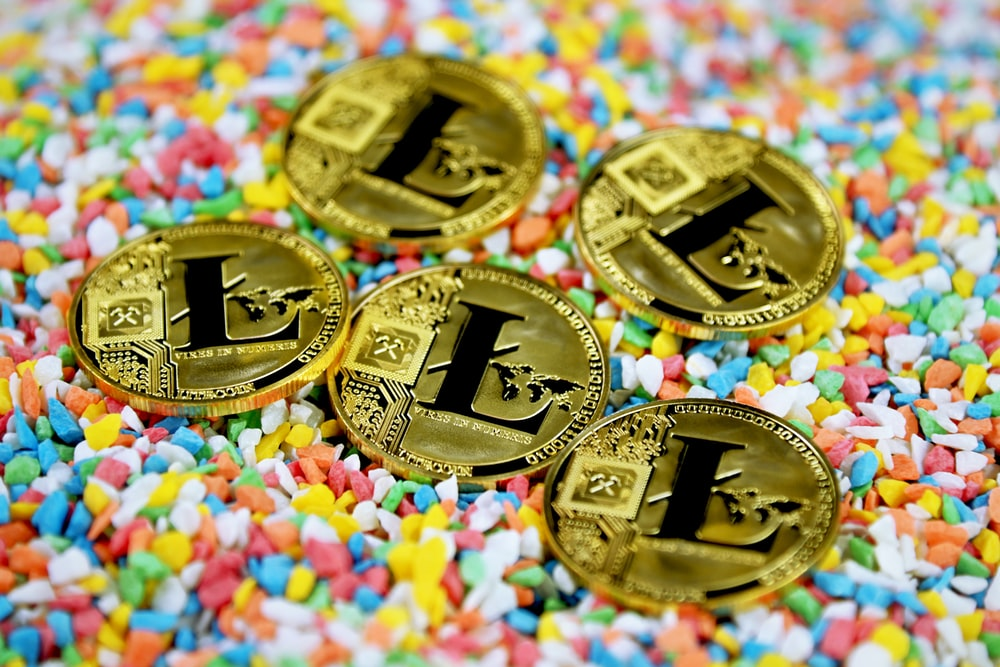 gold round coin on multicolored textile