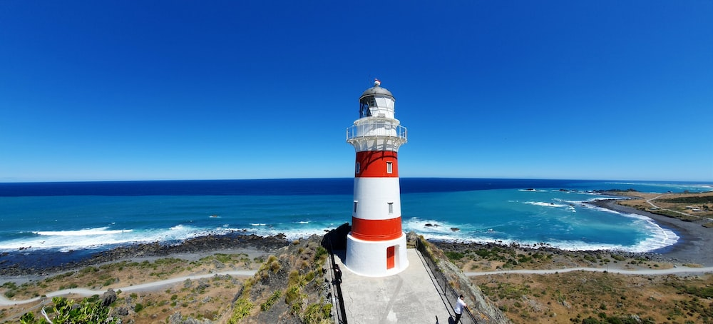 white and red lighthouse near sea during daytime