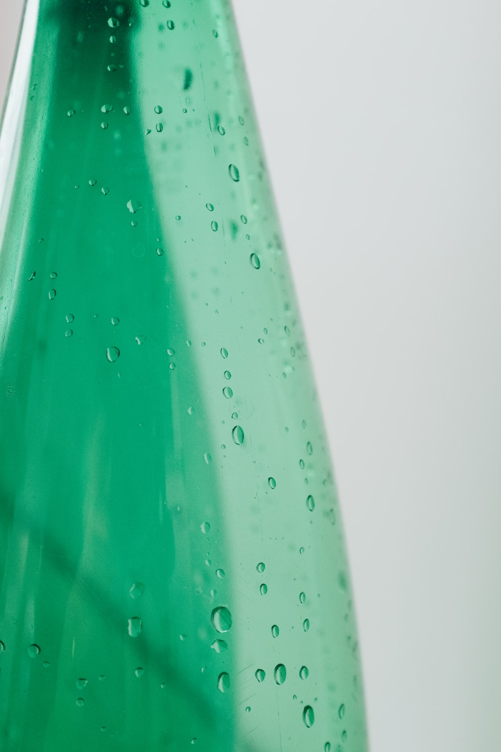 green plastic bottle with water droplets