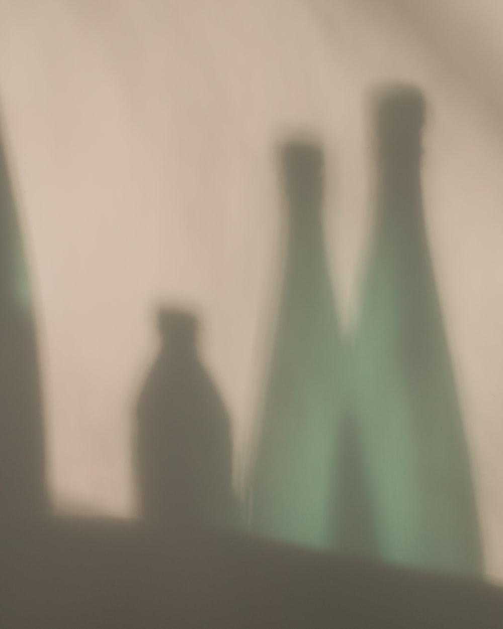 green glass bottle on white table
