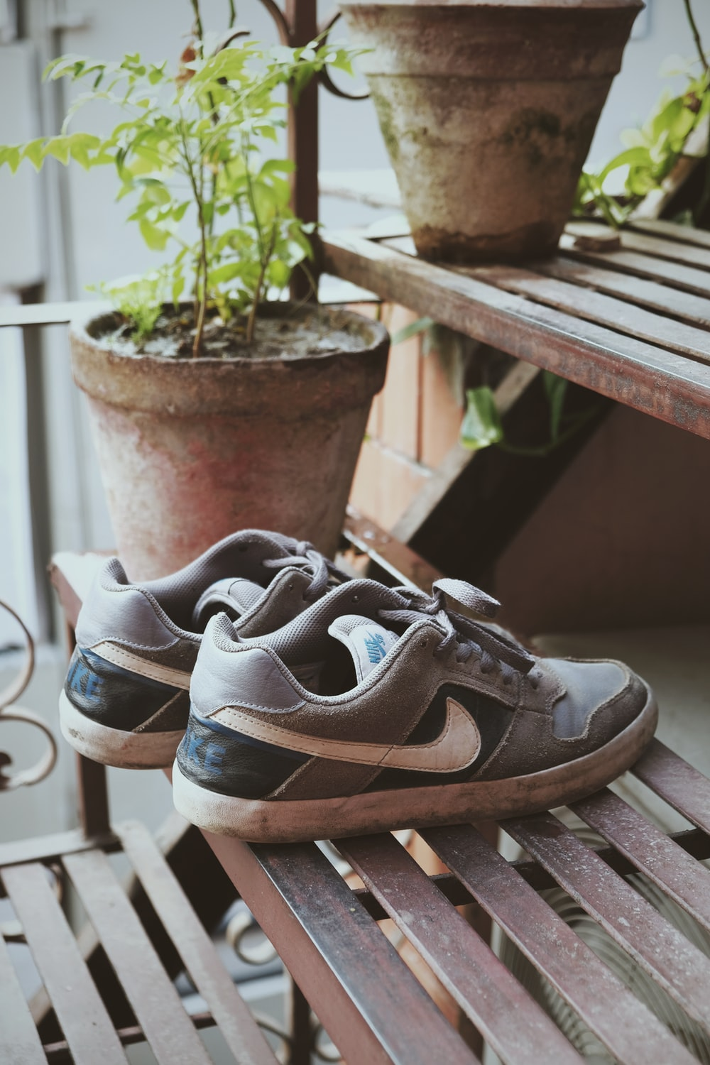 black and white nike athletic shoes on brown wooden bench