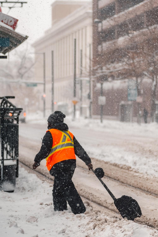 man in orange jacket and black pants walking on snow covered ground during daytime