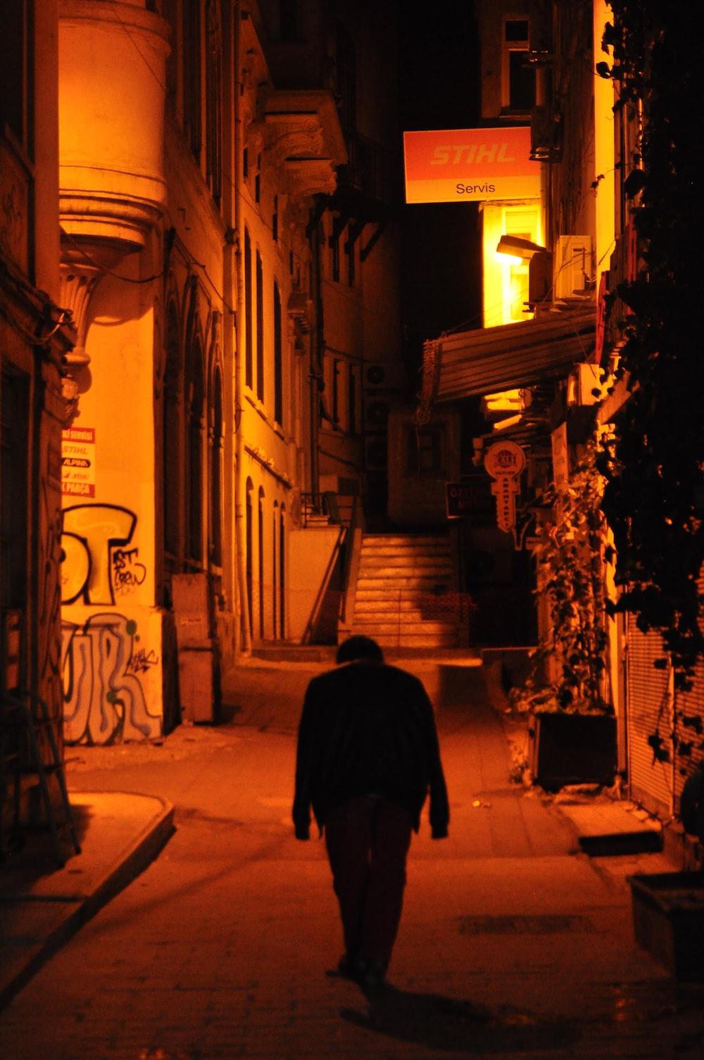 man in black coat walking on street during nighttime