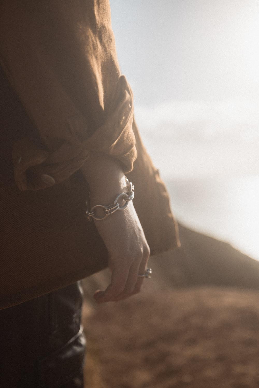 person in black long sleeve shirt wearing silver bracelet