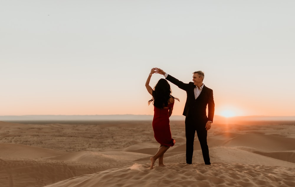 man and woman standing on brown sand during sunset