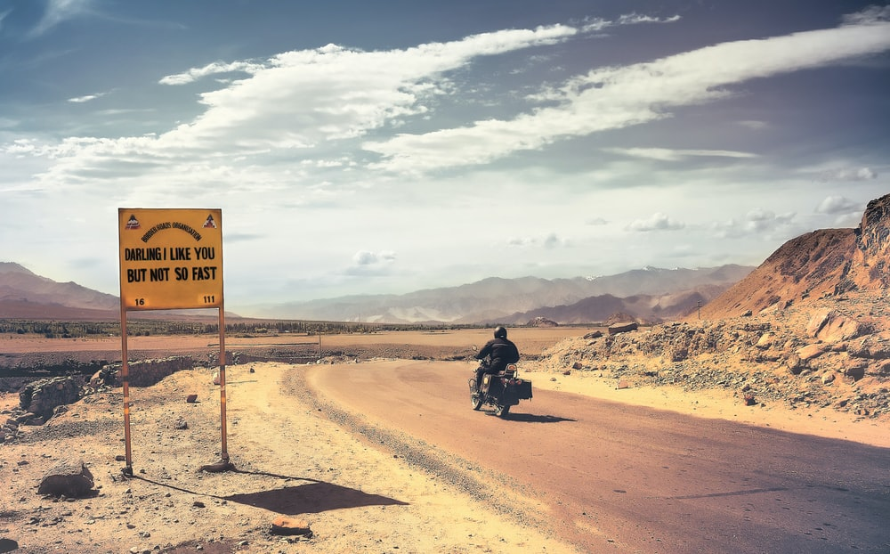man in black motorcycle on brown sand under white clouds and blue sky during daytime