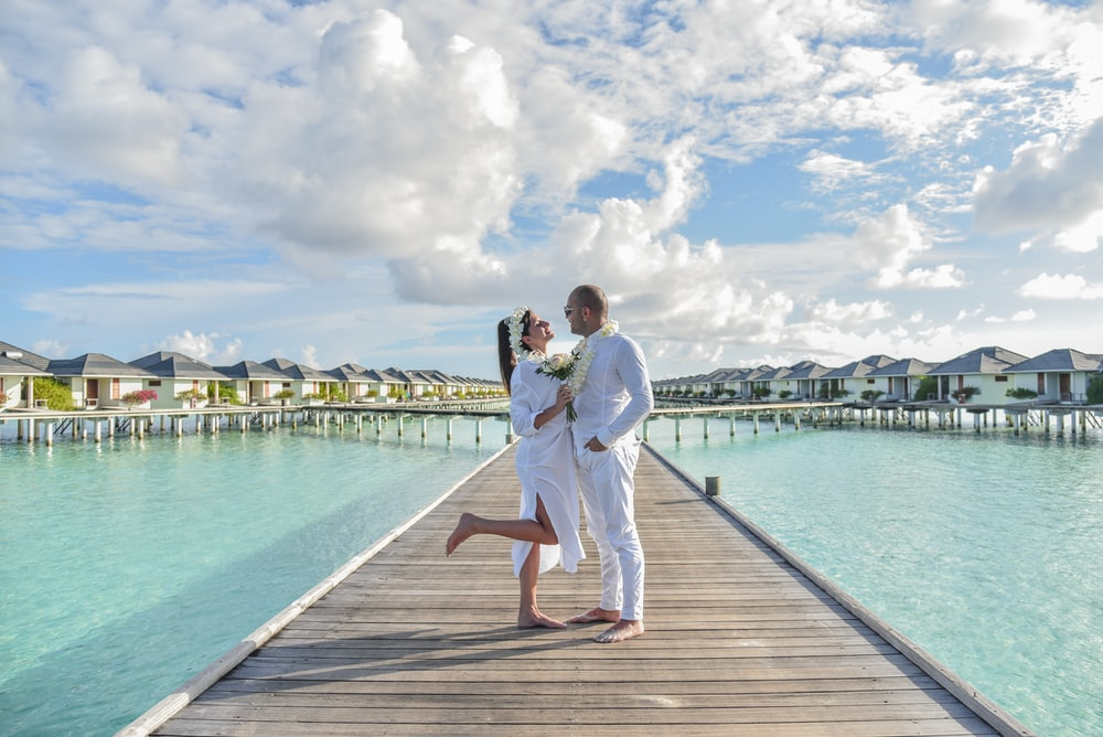 couple standing on wooden dock during daytime