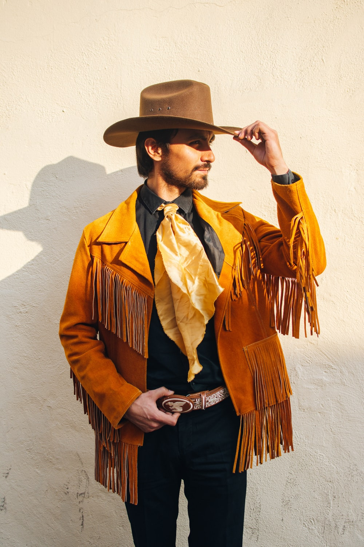 man in brown and black coat wearing brown cowboy hat