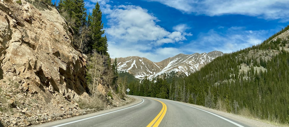 gray concrete road between green trees and white mountains under blue sky and white clouds during