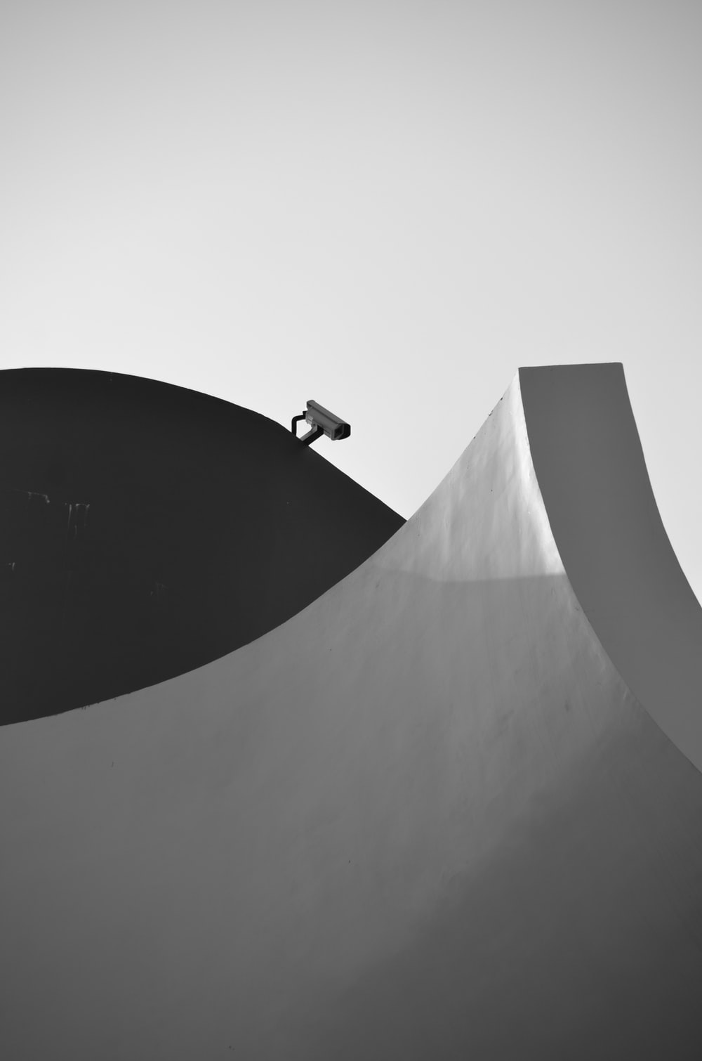 black and white photo of a man walking on a white tunnel