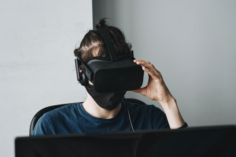 man in blue crew neck shirt wearing black vr goggles
