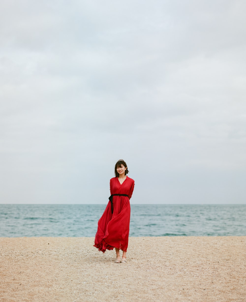 woman in red dress standing on beach during daytime