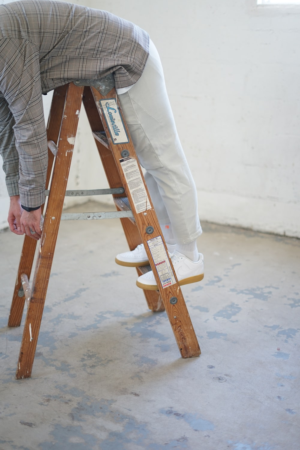 person in gray and white plaid dress shirt and blue denim jeans holding brown wooden skateboard
