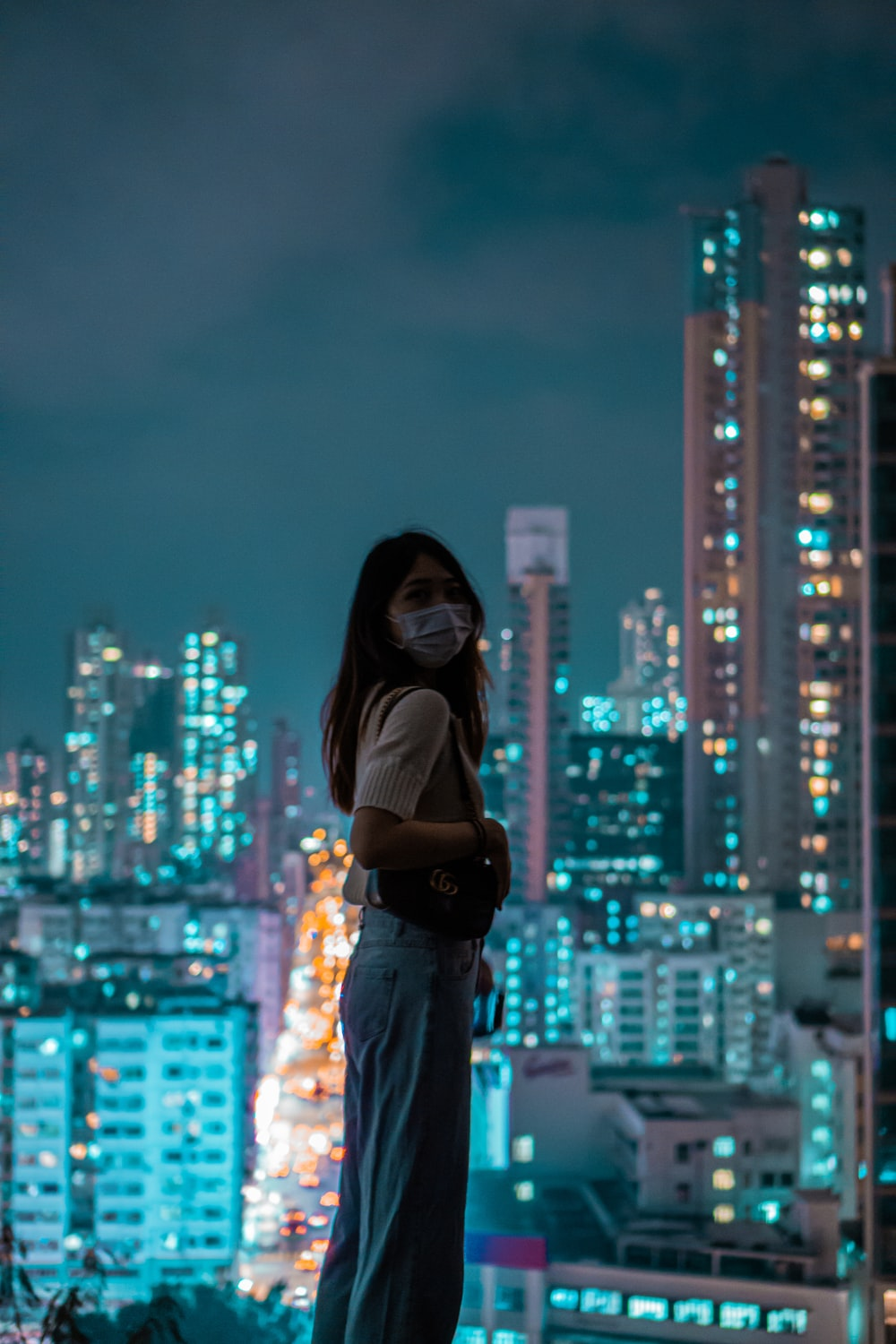 woman in black long sleeve shirt and blue pants standing on top of building during night