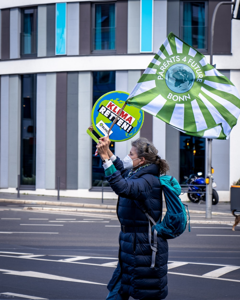 woman in blue jacket holding yellow and green umbrella