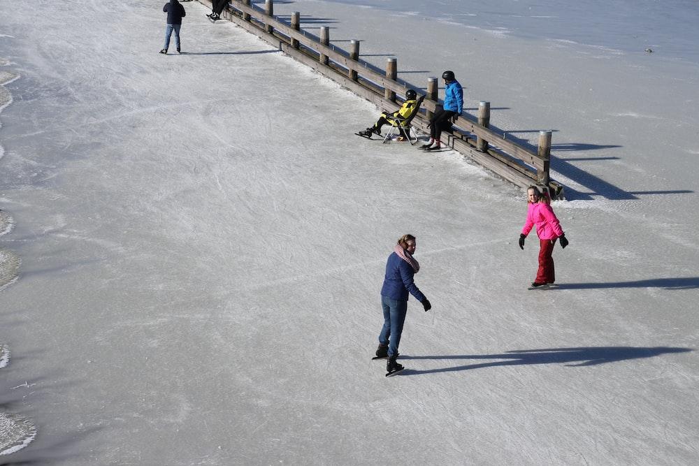 people walking on snow covered bridge during daytime