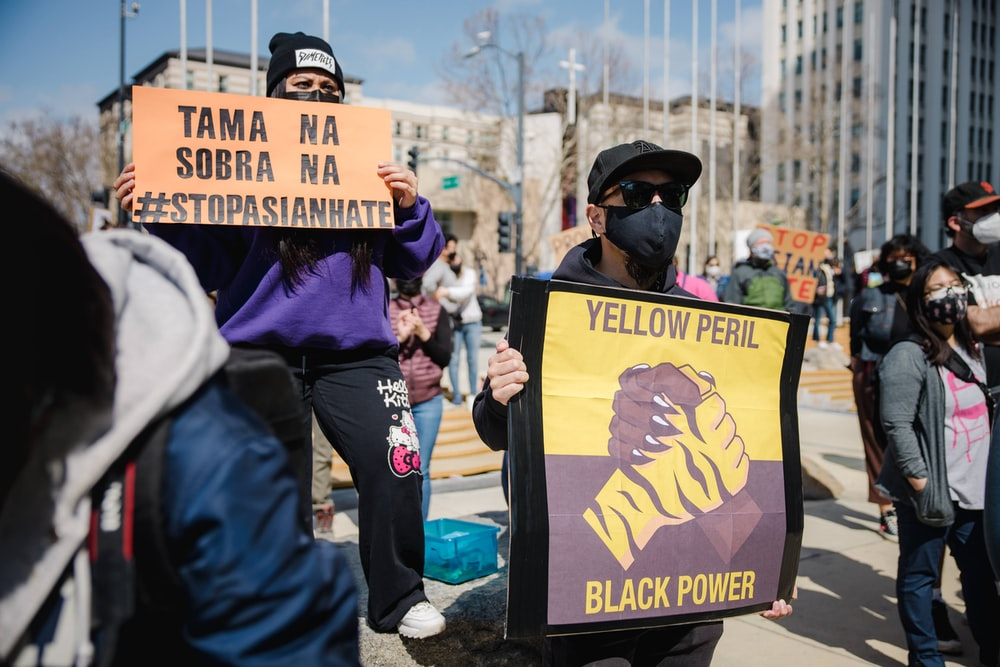man in blue jacket holding black and yellow signage