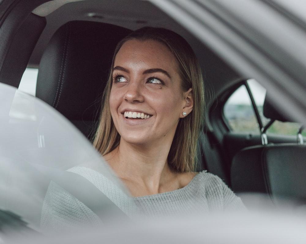 smiling woman in white shirt inside car