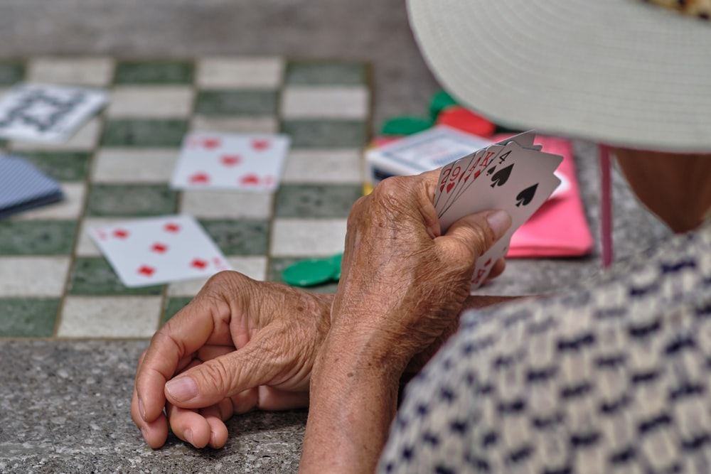 person holding white and black playing cards
