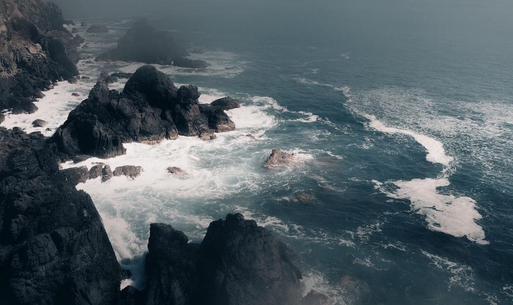 sea waves crashing on rocky shore during daytime