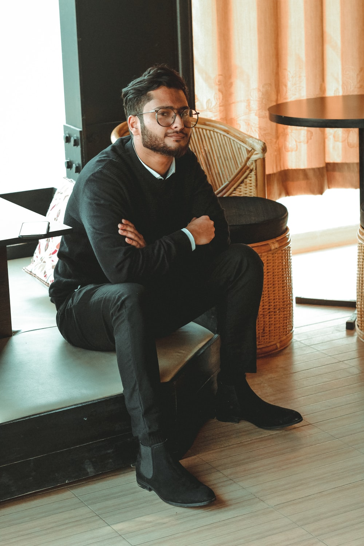 man in black dress shirt sitting on brown chair