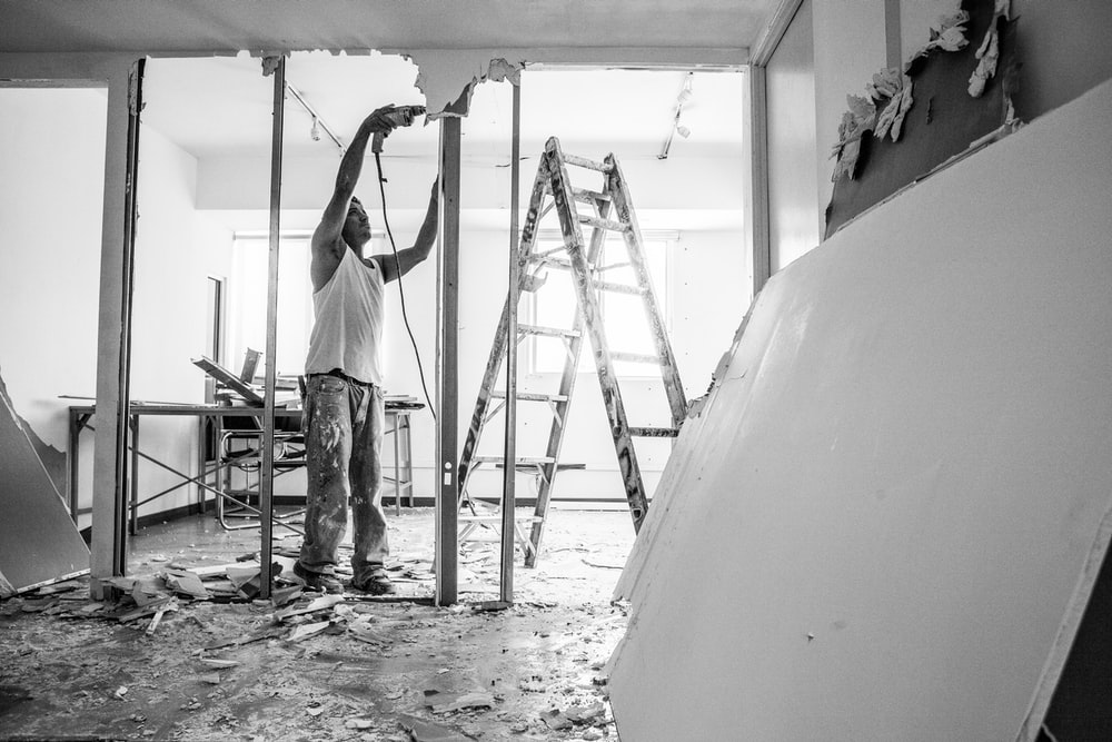 man in white t-shirt and black pants standing on ladder