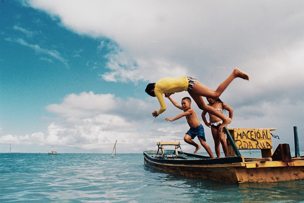 2 women in yellow and blue bikini on brown wooden boat on blue sea during daytime