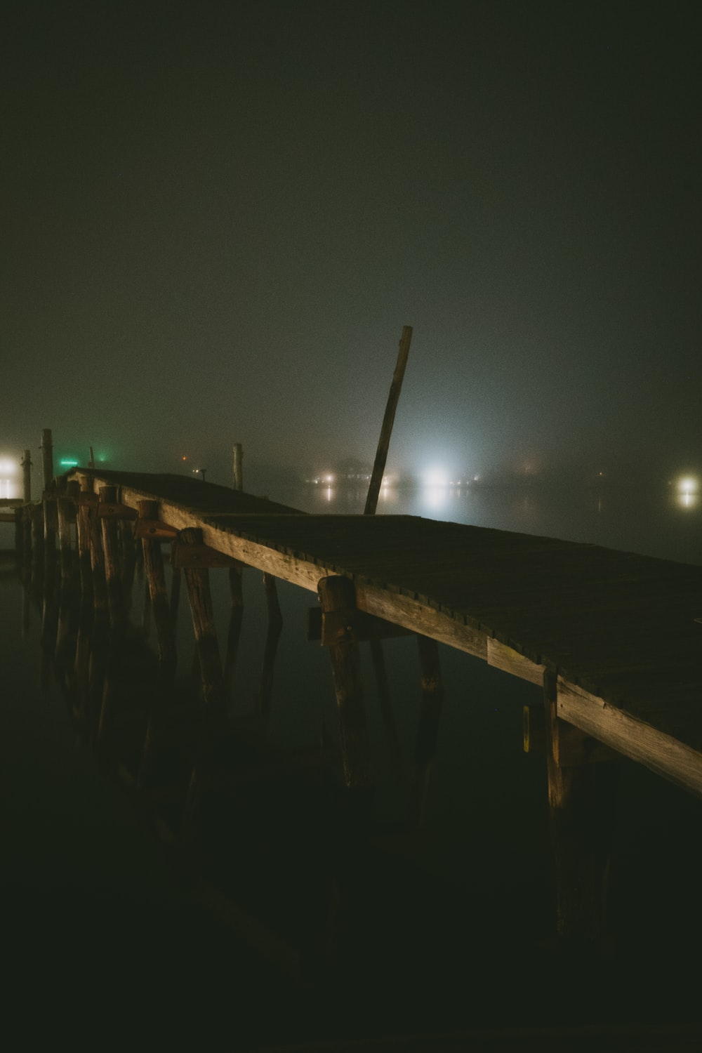 brown wooden dock on sea during night time