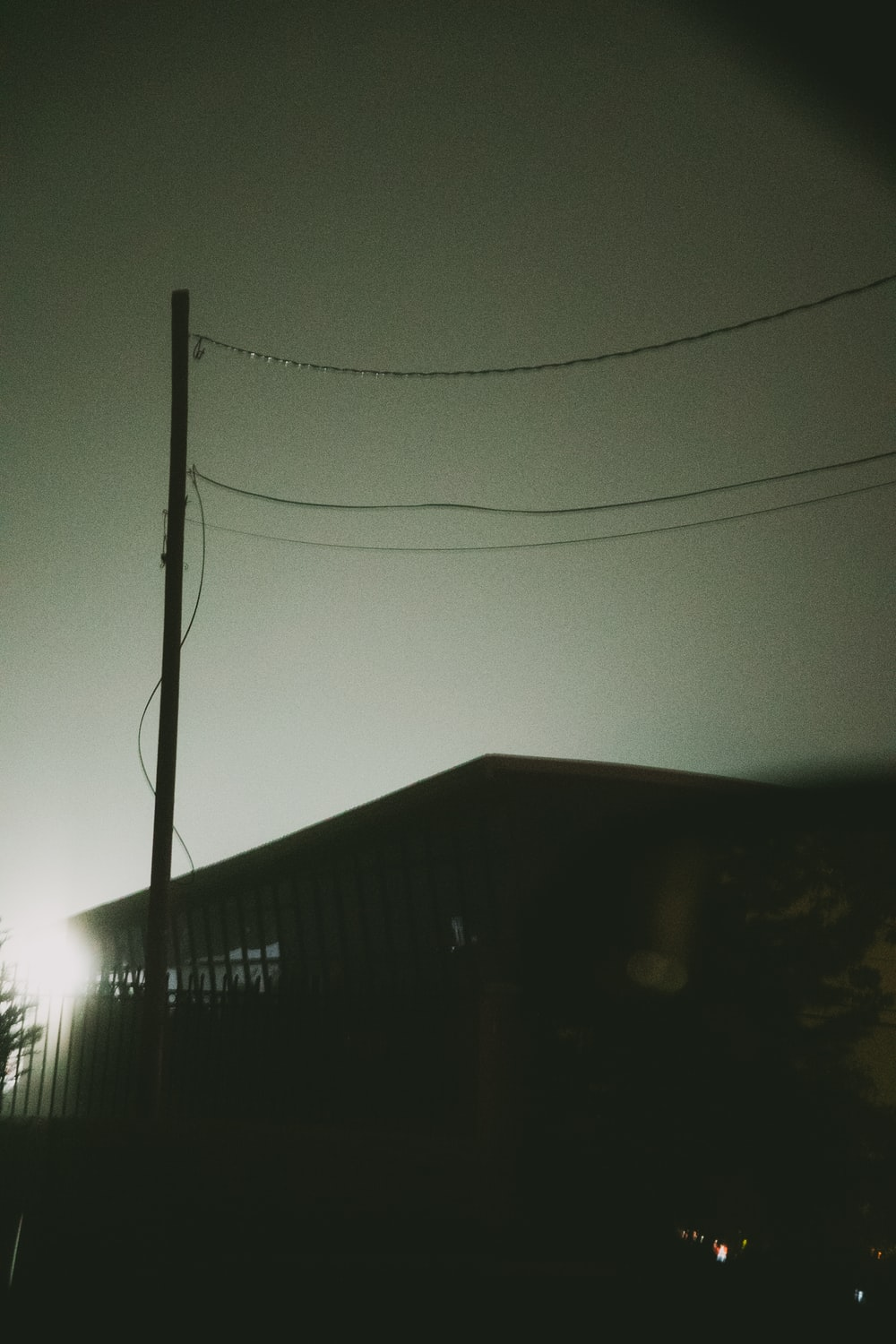 black electric post near house during night time
